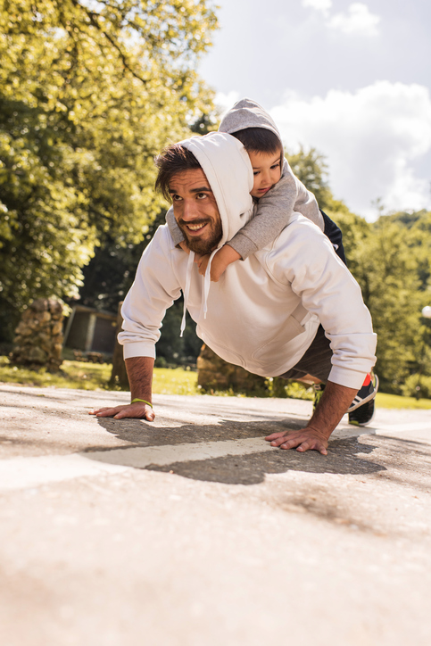 Young smiling father holding his son on back and exercising push-ups in the park.