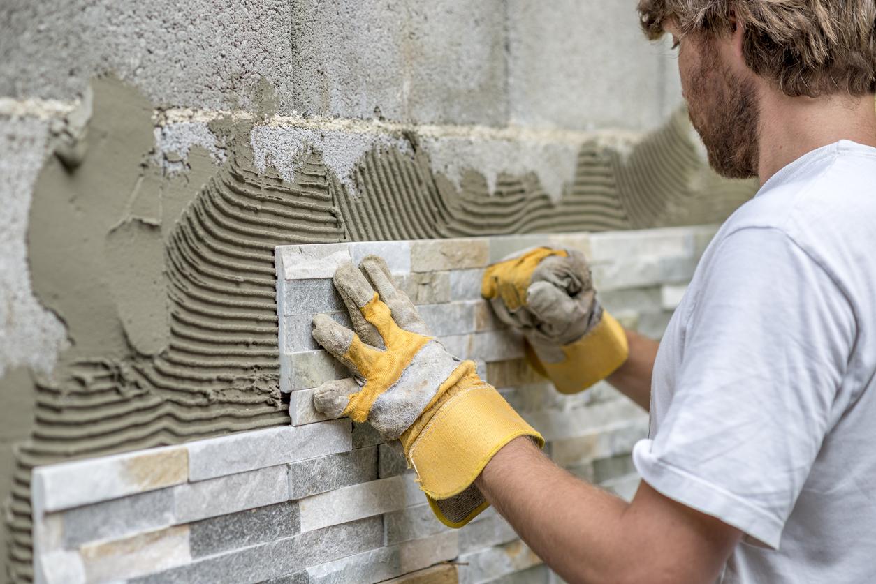 Man pressing ornamental tile into a glue on a wall