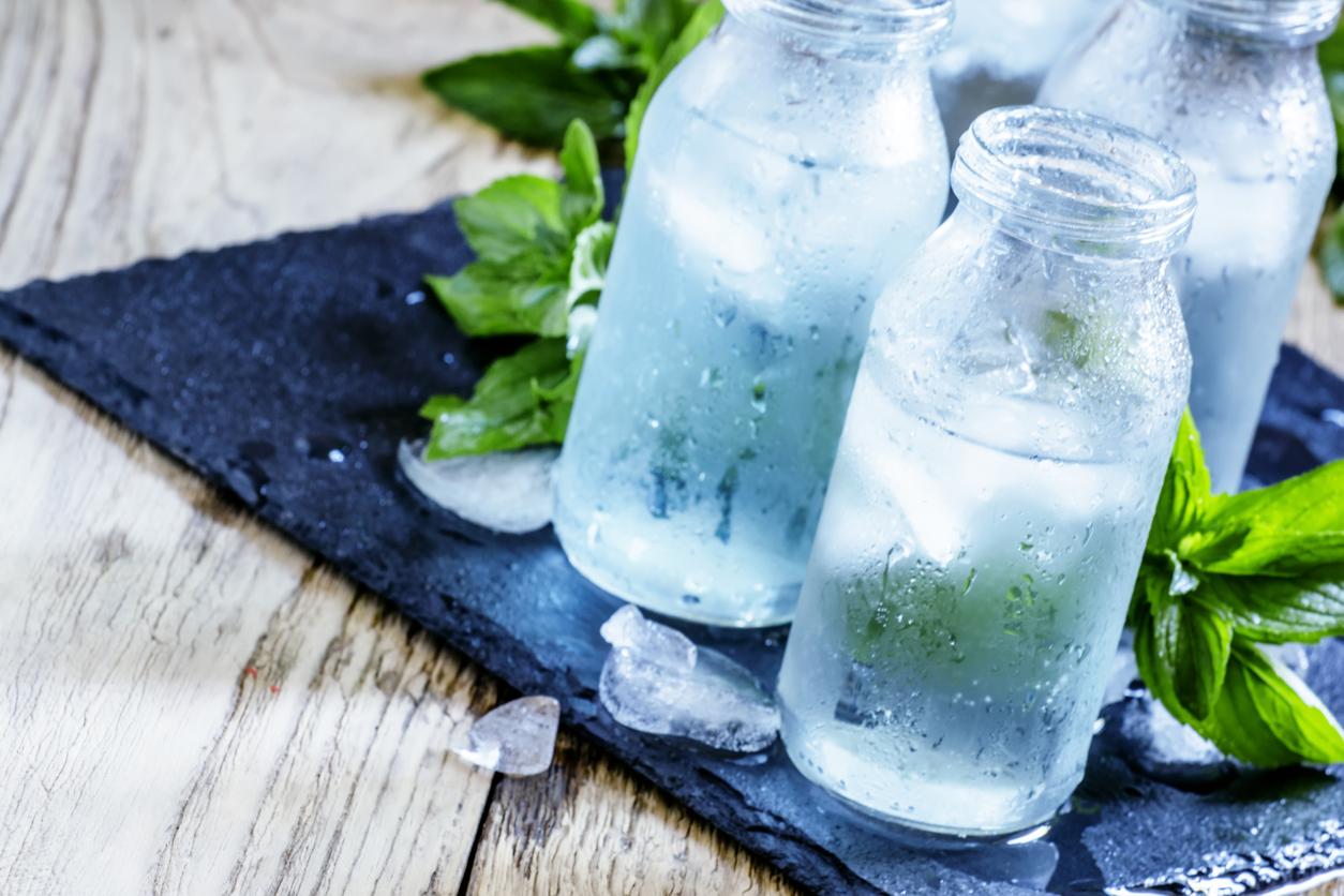 Iskaldt vann med mynteblader på bordet.